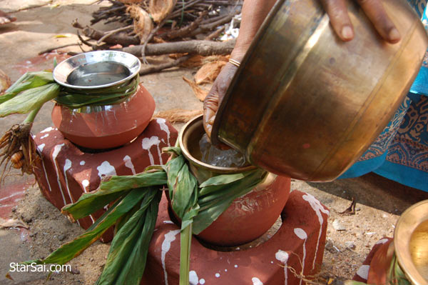 Mom pouring water in Pongal pot
